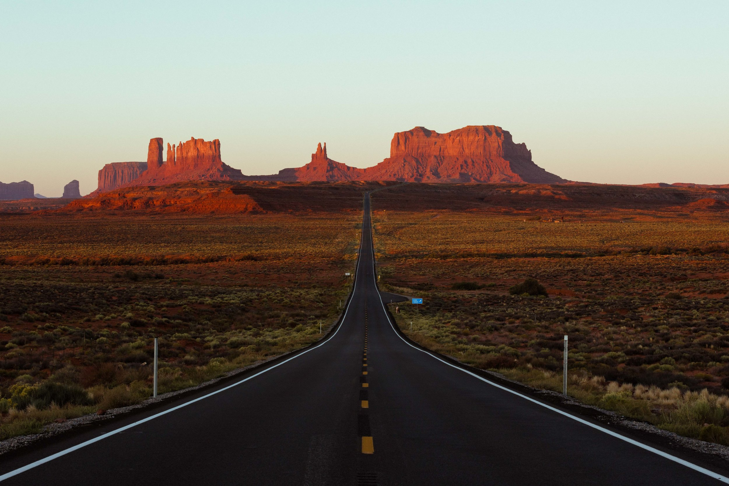 The sun rising over Monument Valley Road
