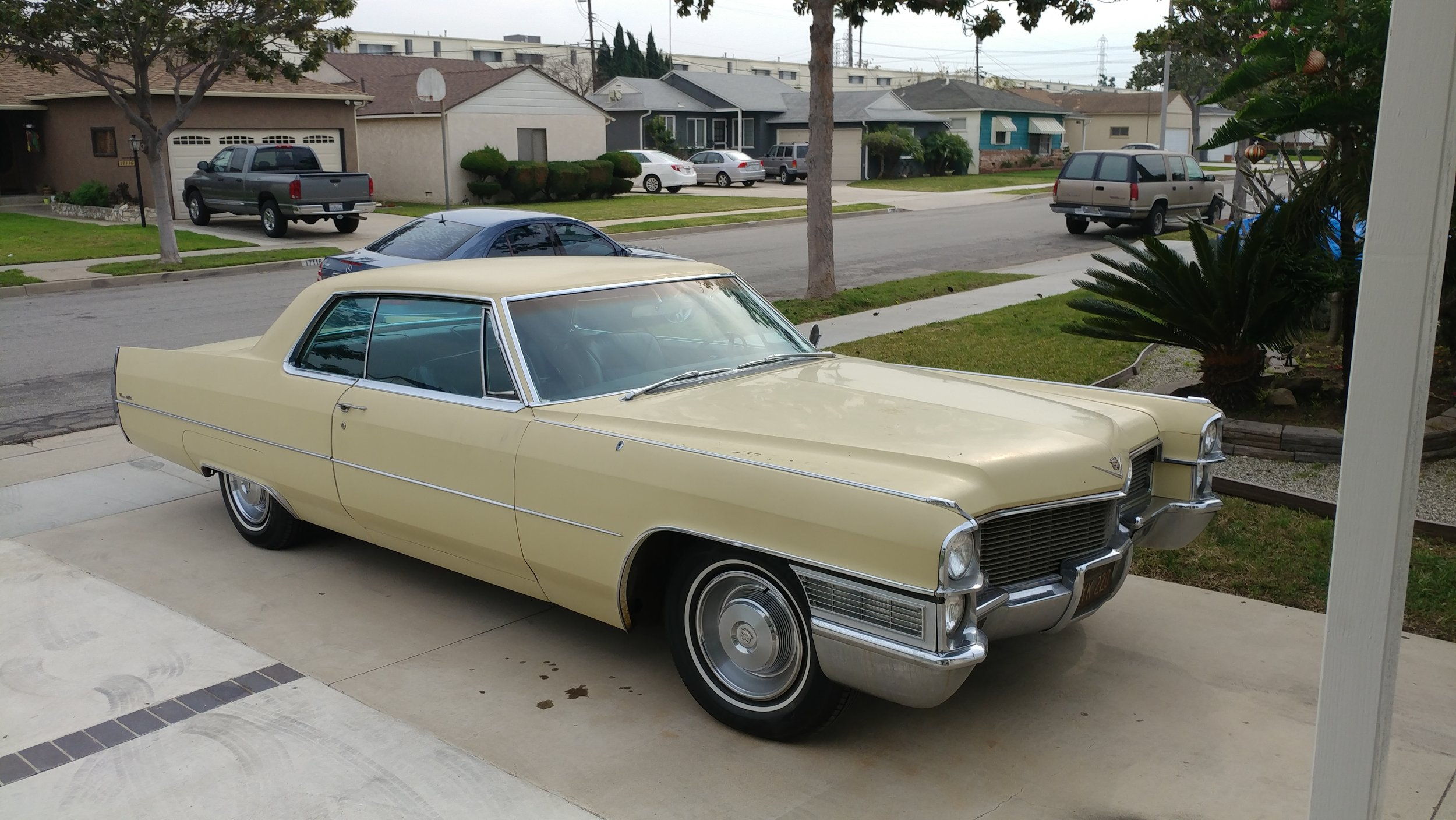 """1965 Cadillac Coupe Deville - """"This cream vehicle with navy blue interior was purchased in 1967 the same year our Parents purchased their first home. She replaced the 1955 Century Buick taking my Dad to and from work every day 30 miles one way. He enjoyed the smooth ride, the cool air conditioning, and plush leather seats."""""""