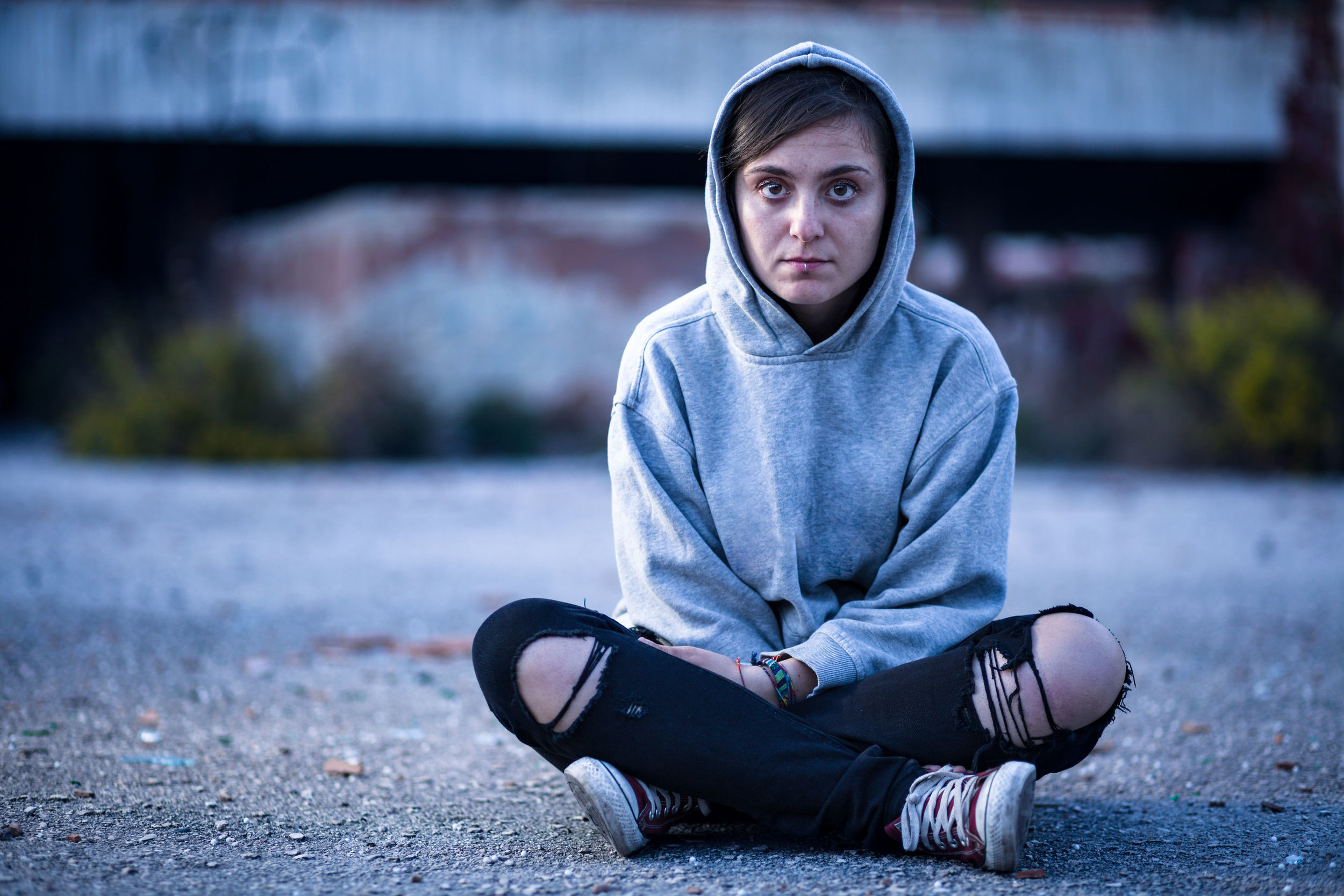 Woman with Sweatshirt and Torn Trousers Sitting on the Street.jpg