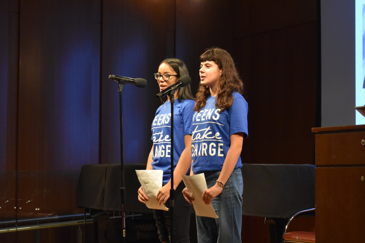 Tiffani Torres (left) and Sophie Mode (right) present spoken word testimony about the differences in their school experiences.  Photo by Julian Giordano