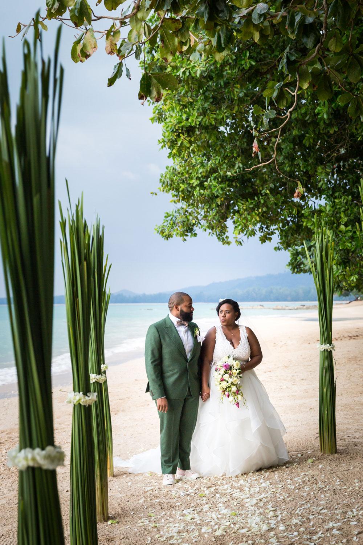 Bride and groom walking on Thailand beach