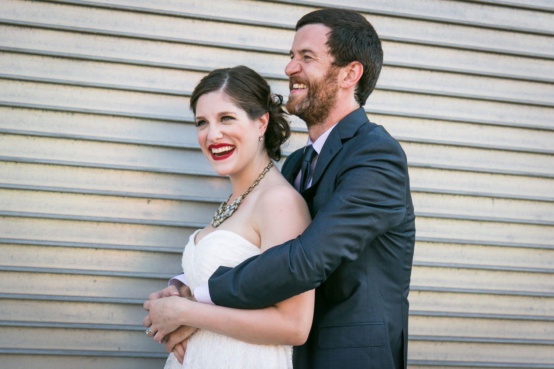 Bride and groom hugging against metal wall