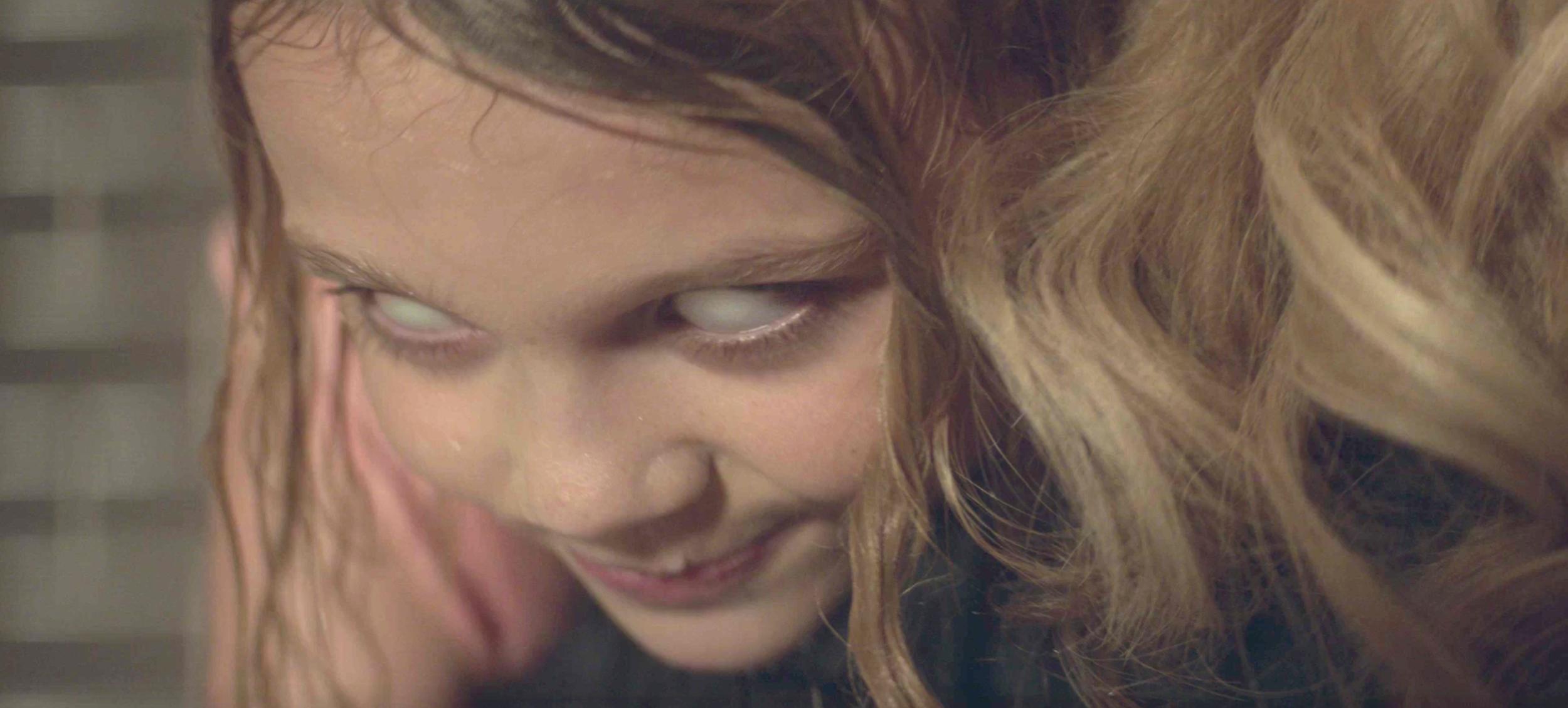Milky white eyes absent pupils and devilish little smile, yup, she's possessed!