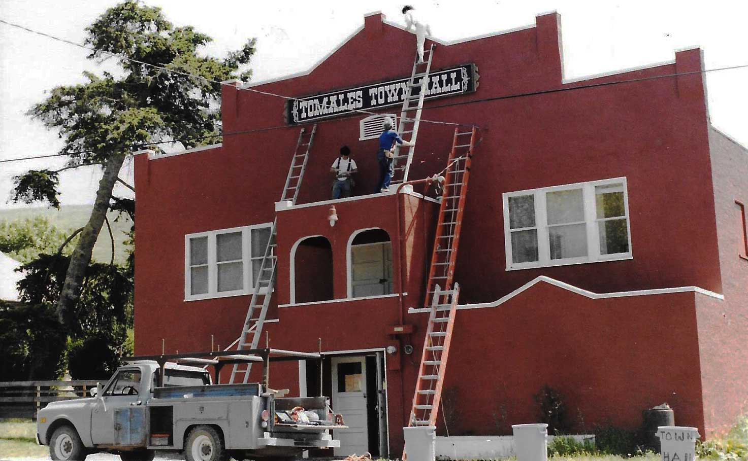 Volunteer crew painting the Town Hall red, c. 1970s.