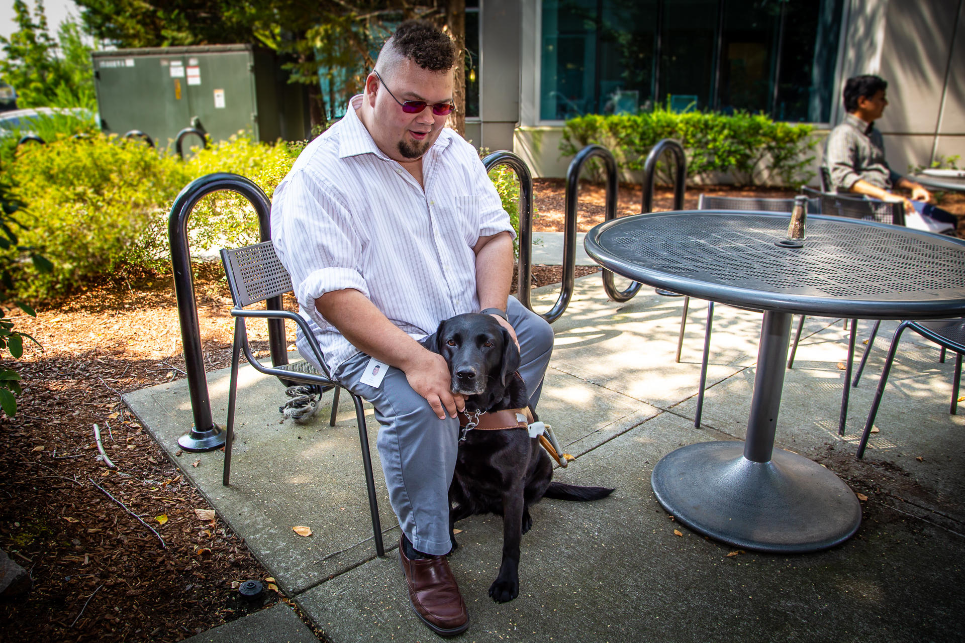 Cory Joseph, a software engineer and accessibility lead with a passion for empowering every Microsoft employee, sits with Vine, his guide dog. (Photo by Jim Adams | Showcase)