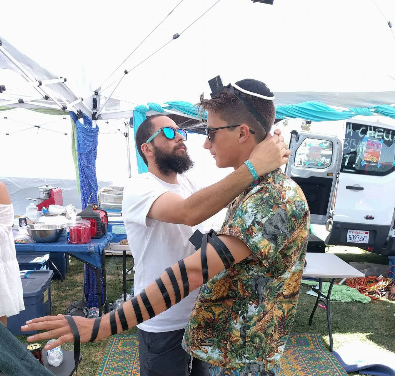 Wrapping Tefillin with a visitor at the Coachella Music Festival.