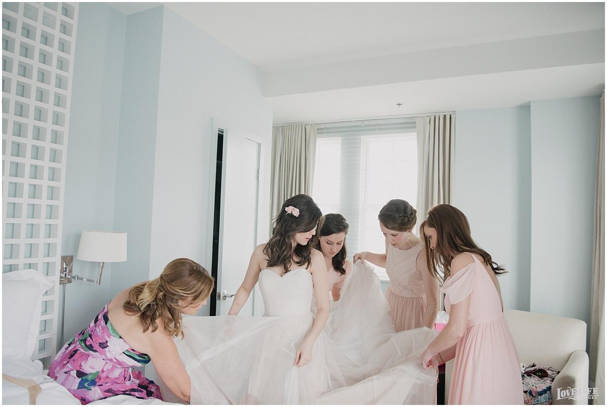 lorien hotel bridesmaids helping bride into dress.JPG