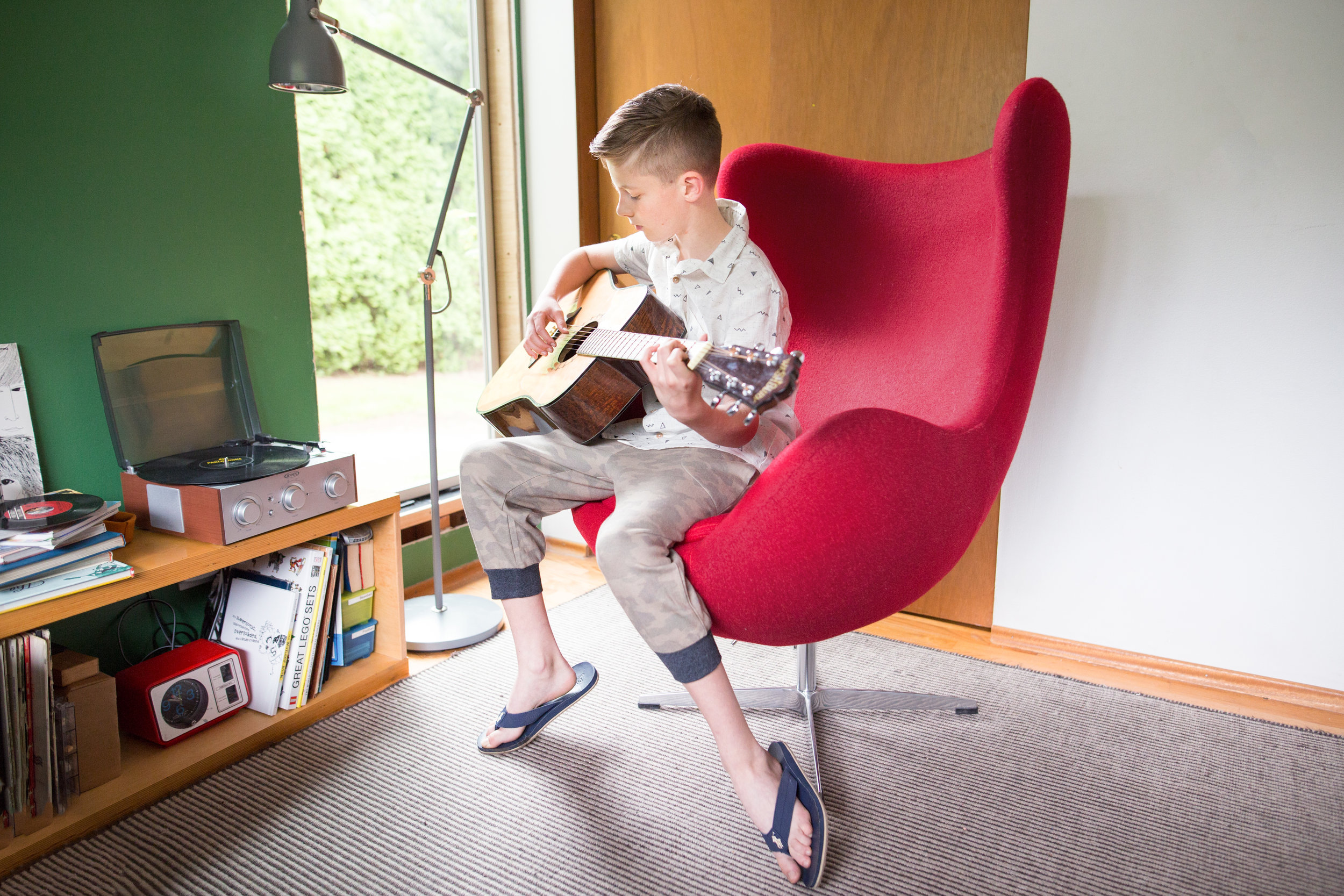 teenaged boy in room, playing guitar, family photo shoot