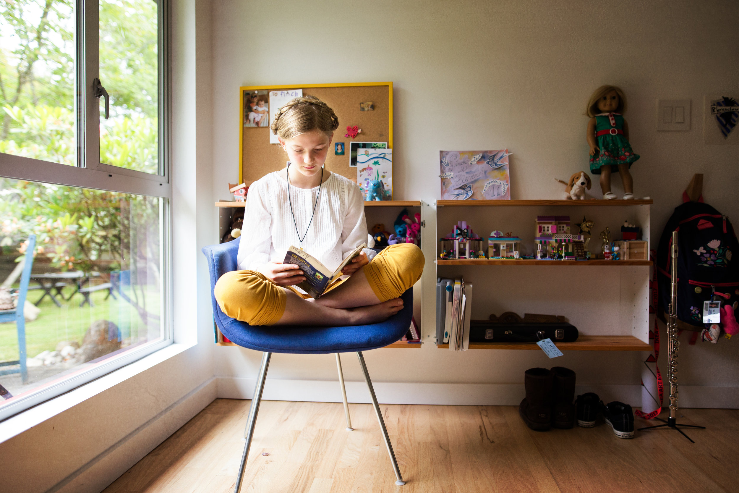 teenaged girl sitting on modern chair at window reading, family photography