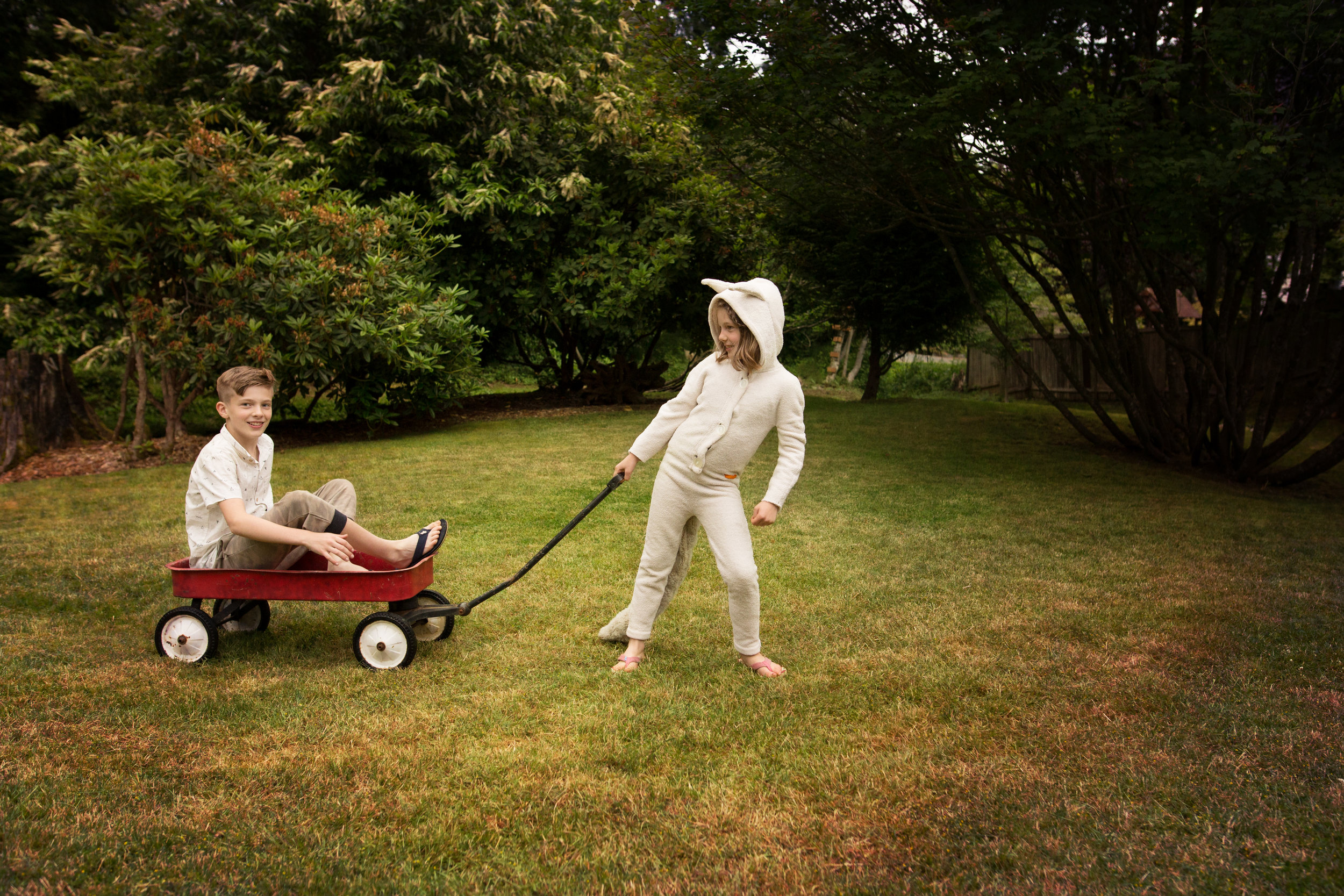 young girl in wild things costume pulling teenaged boy in wagon in green yard