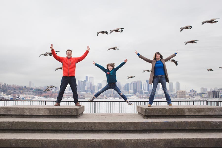 family of 3 jumping, gasworks park, city scene, flying geese