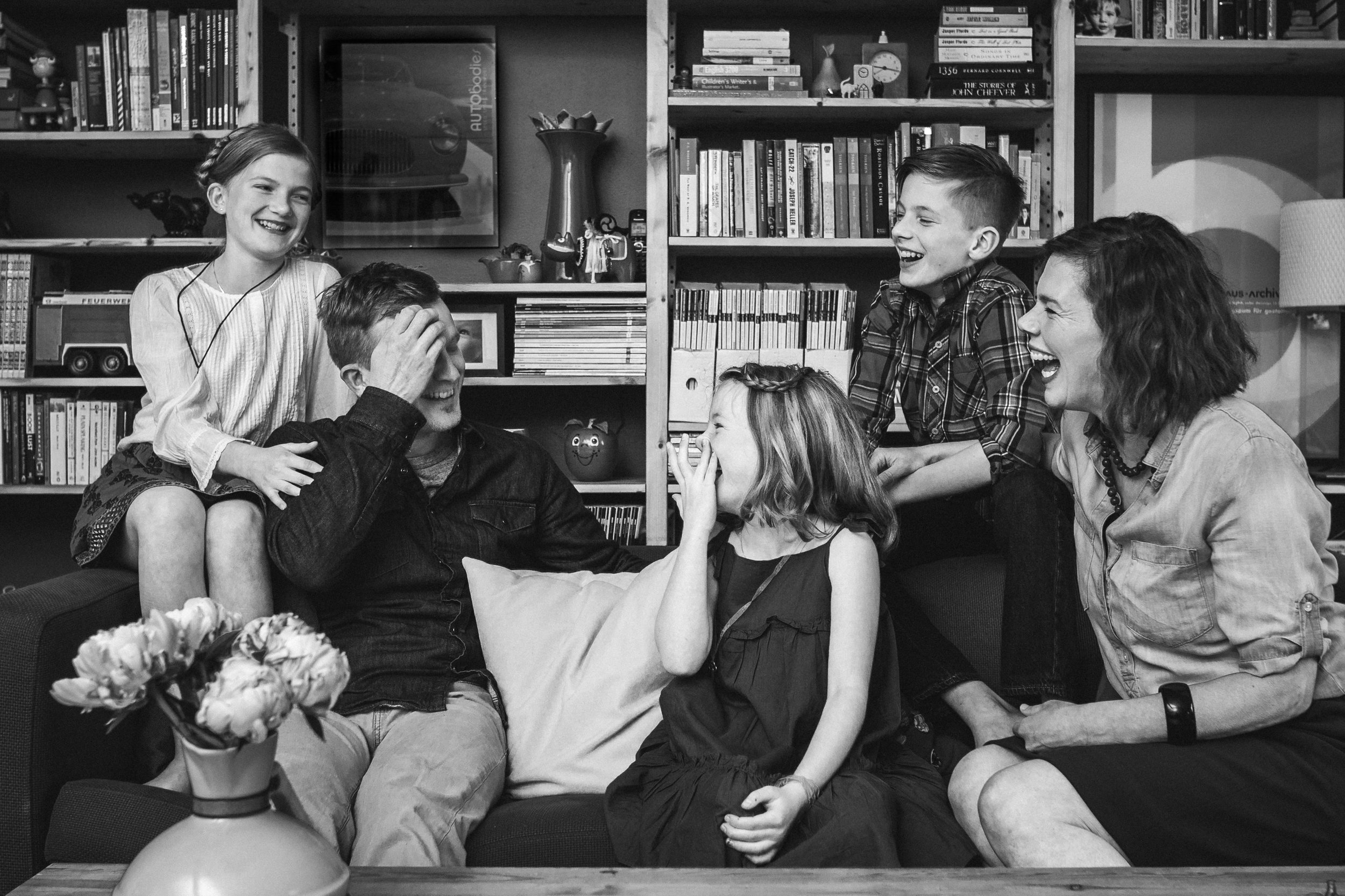 black and white family of 5 on couch in front of bookshelf laughing and looking at each other