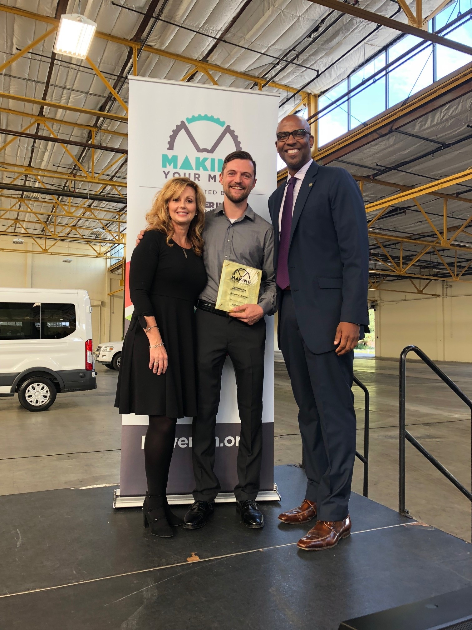 - Michael Patterson, CEO of Liquid Flower was presented an award for winning the 2nd Annual Making Your Mark competition. Also shown is Power Inn Alliance's Executive Director Tracey Schaal, and guest emcee Louis Stewart, Chief Innovation Officer at the City of Sacramento Mayor's Office for Innovation and Entrepreneurship.