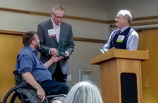 Barry Long, left, and Tom Minty, at podium, presenting the Northwest Access Fund Best Practices Award on behalf of the Northwest Multiple Listing Service last fall.
