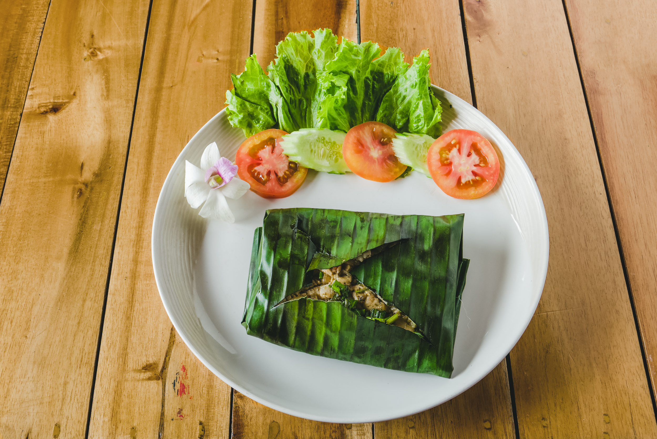 »BARRACUDA IN BANANA LEAF« - People from all over the area come to our restaurant to enjoy our specialty:a fresh barracuda filet steamed in a recently chopped banana leaf with a combination of herbs and spices. Try it yourself and be prepared to order it not only once.