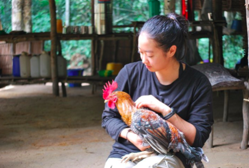 Holding a chicken at a field site in Congo.