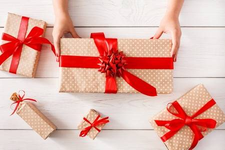88397858-diy-hobby-womans-hands-give-wrapped-christmas-holiday-handmade-present-in-paper-with-red-ribbon-pres.jpg