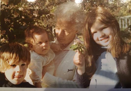 Mum, shortly before her death, aged 62. My eldest daughter proudly holds some apple blossom and the greenhouse stands in the background.