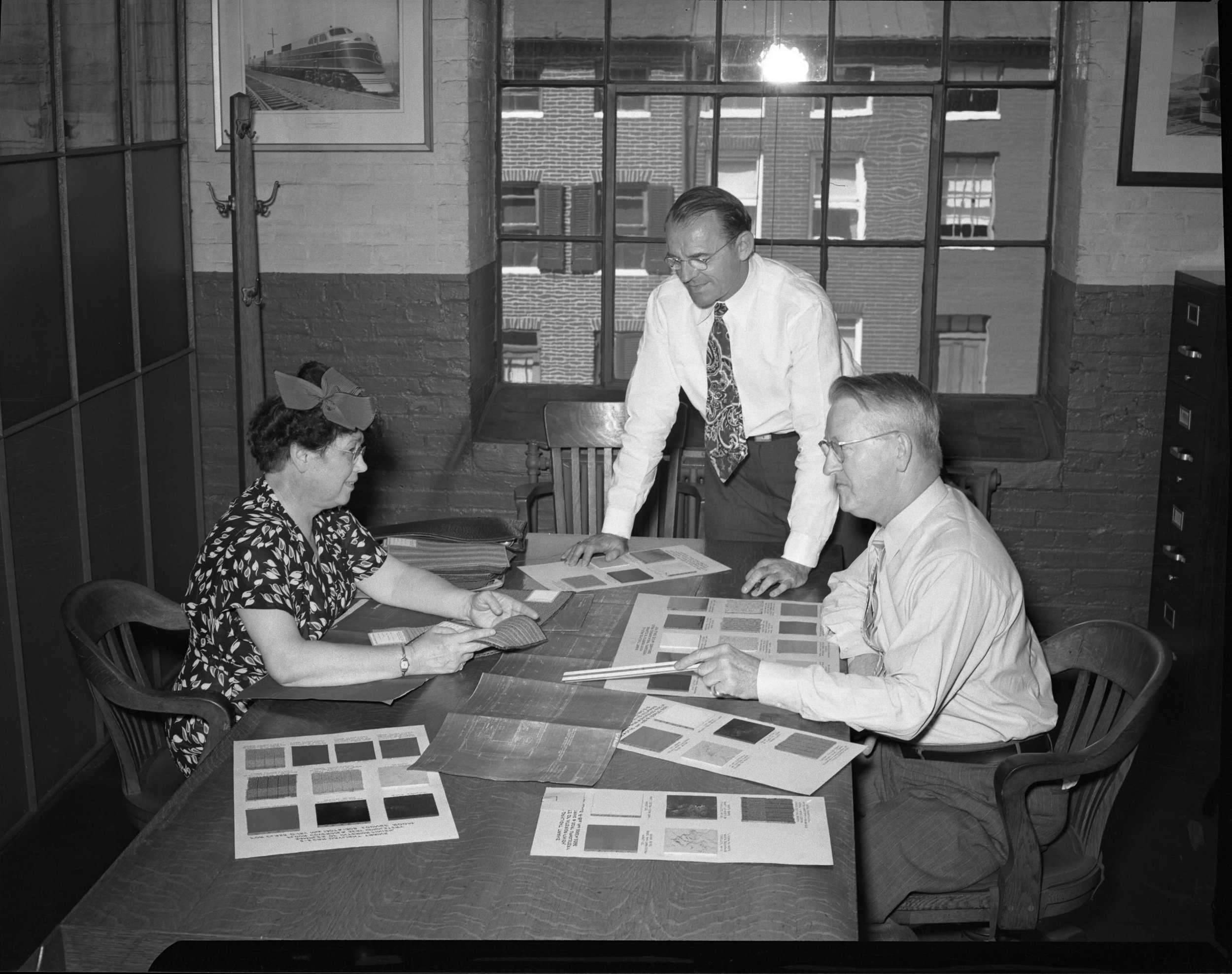 Service Engineer Olive Dennis consults with Alden B. Lawson, Assistant Engineer, Motive Power & Equipment (standing) and Frederick H. Einwaechter, Chief Engineer, Motive Power & Equipment (seated). The photograph was taken in the Mechanical Engineering Department at Mt. Clare, around 1947-1948.  Photo courtesy of the  B & O Railroad Museum