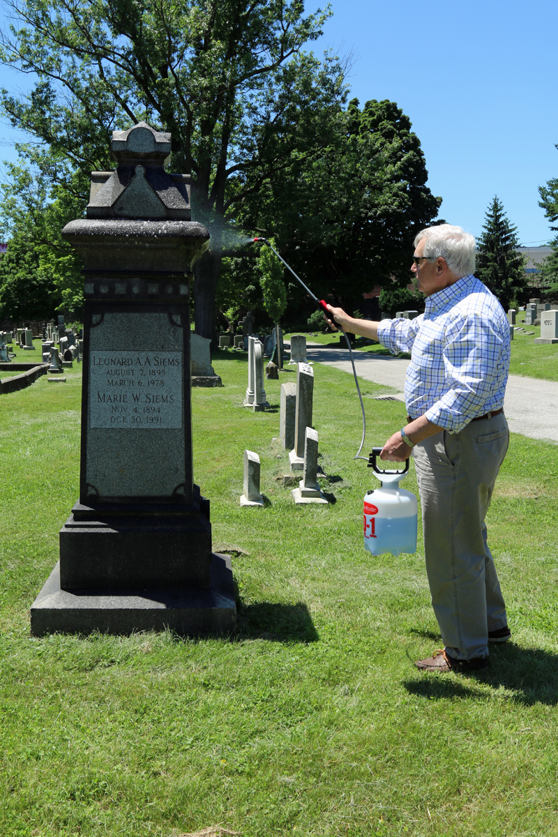 Dying to Tell Their Stories  blog author Richard Berglund removing lichens and moss from his maternal great-great grandparents' grave stone in Green Mount Cemetery.