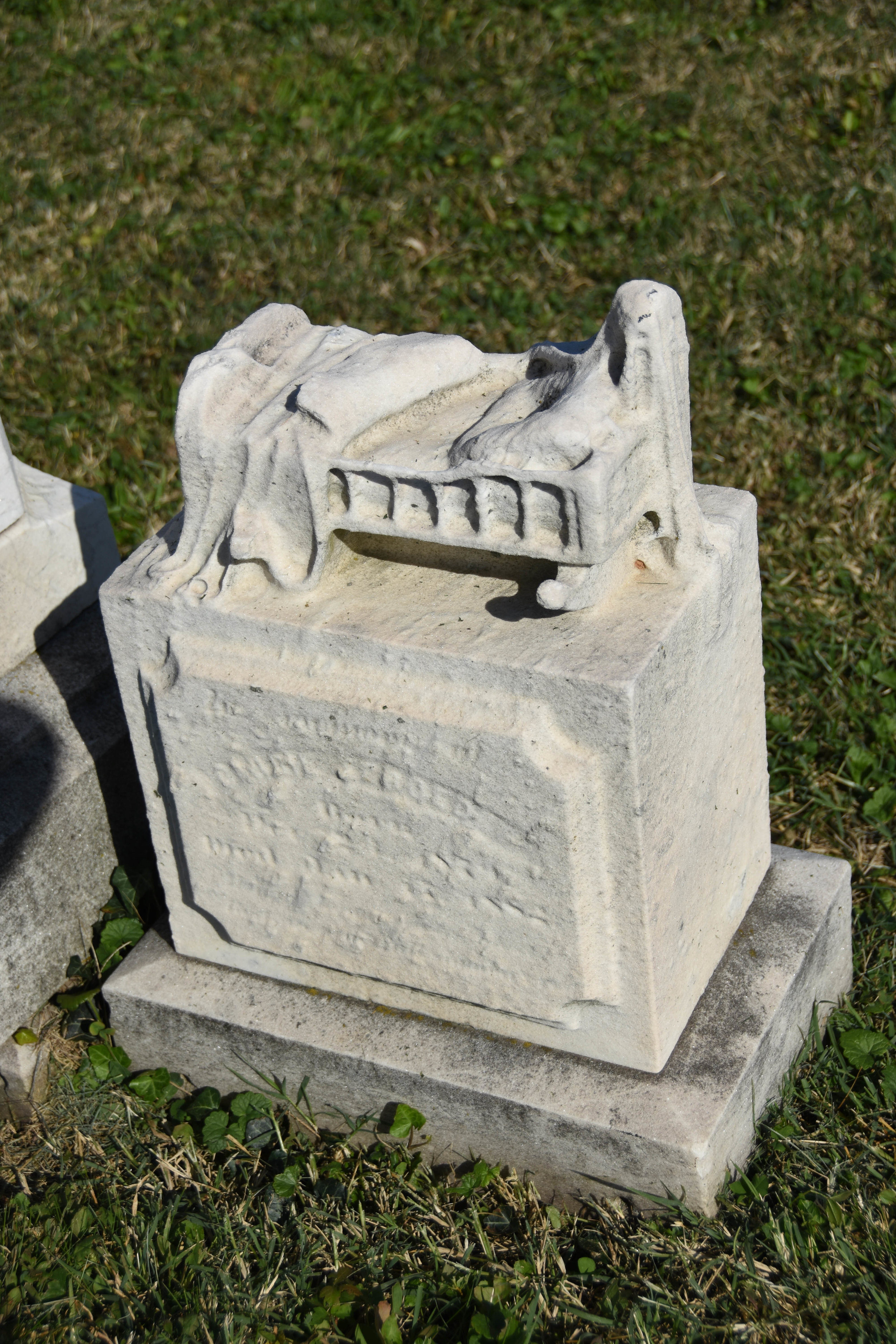 An sculpture of a crib, worn by time, is still visible atop this stone at Baltimore Cemetery.