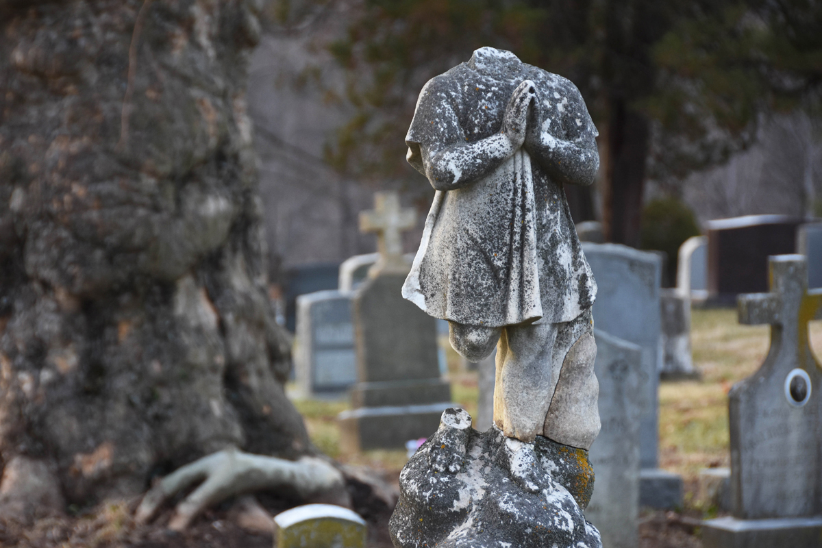 Time and the elements wear away grave markers, like this praying child who is missing a leg and a head, located at Woodlawn Cemetery.
