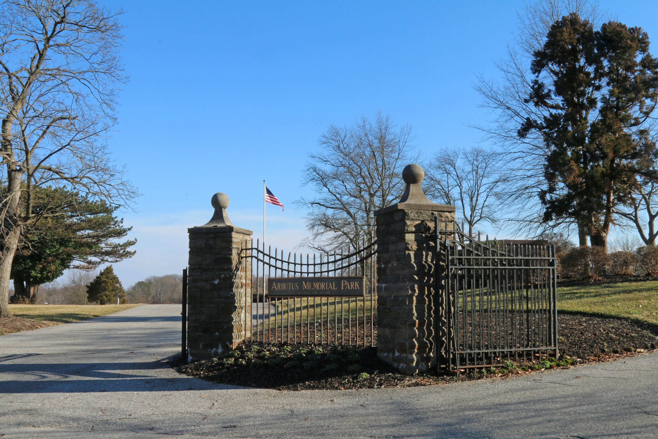 An American flag waves against blue skies beyond the entrance gate to Arbutus Memorial Park. Photo by Richard Berglund