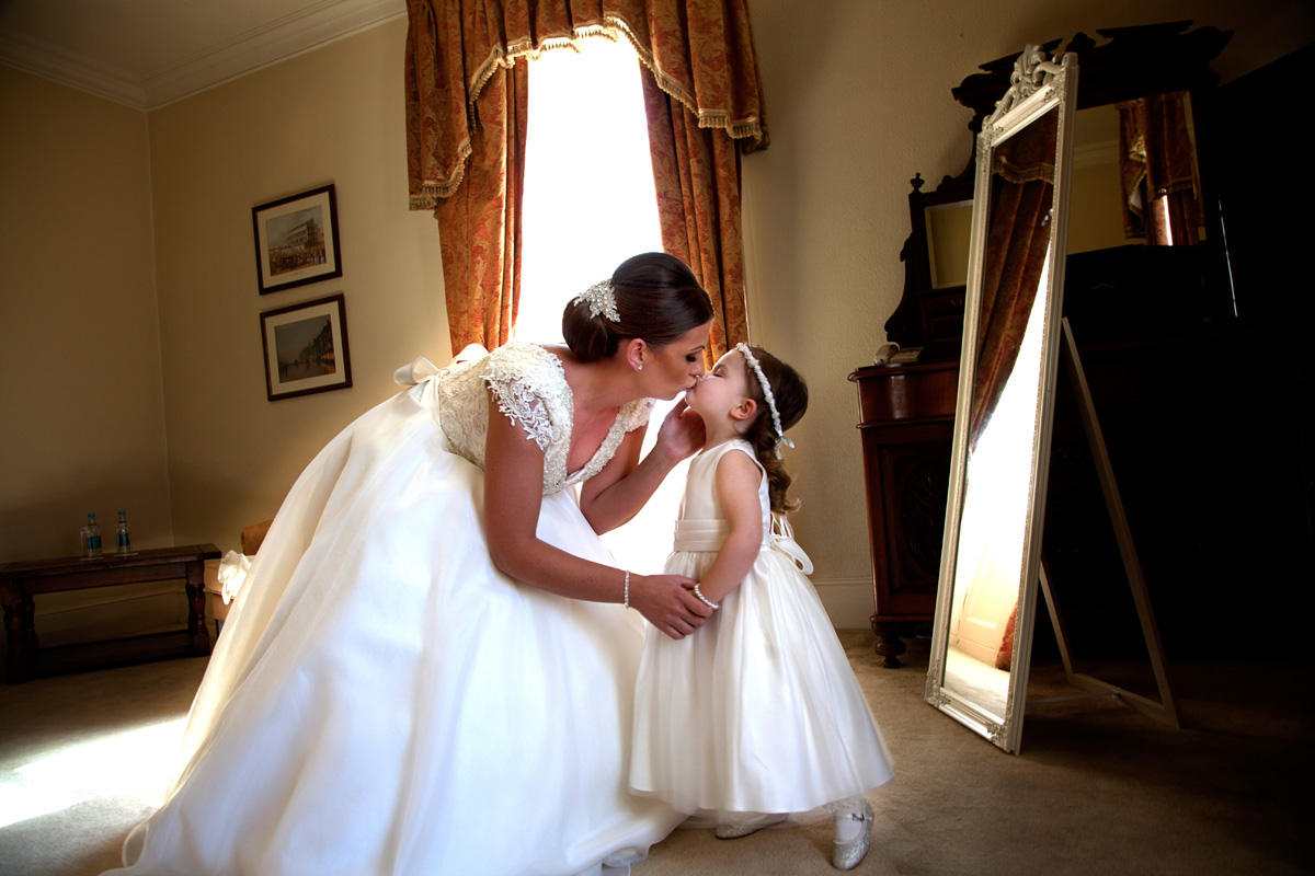 A kiss between bride and daughter at the Mulberry House, Ongar. Essex wedding