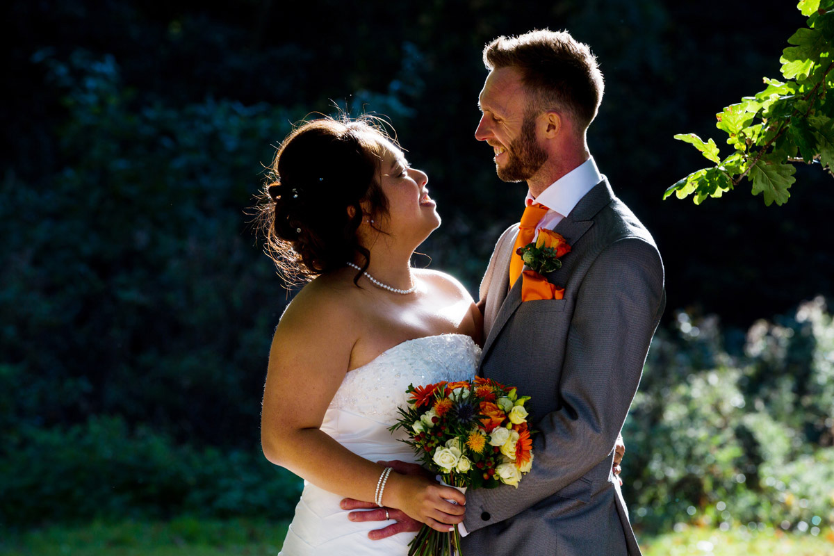 Bride and groom backlit by sunshine at their Essex wedding