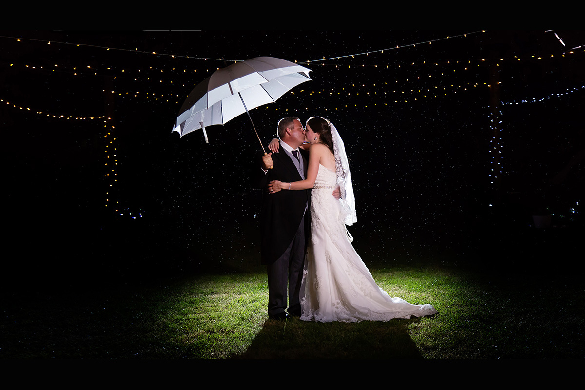 A kiss in the rain for the bride and groom at their Suffolk wedding