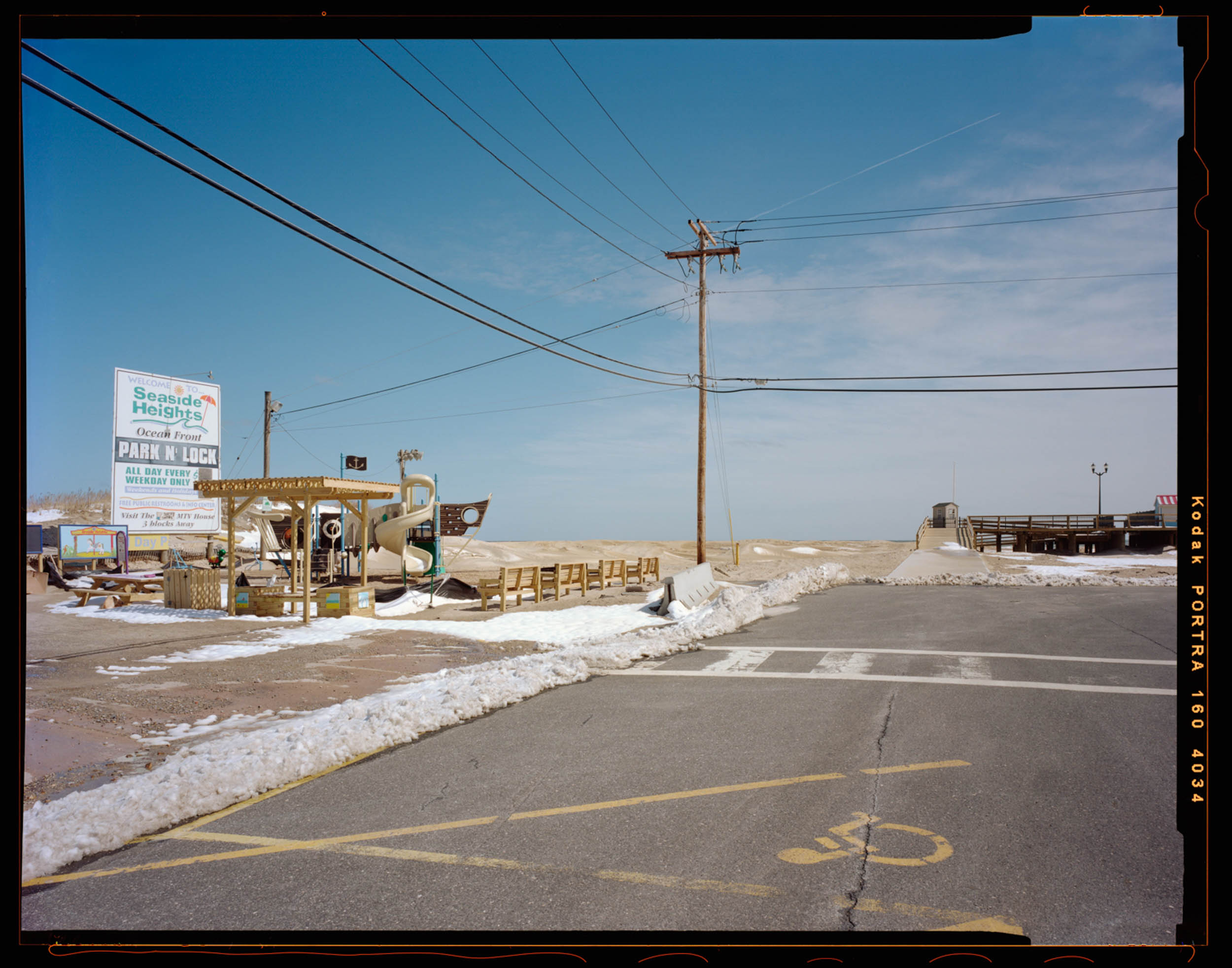 Park and Ride, Seaside, NJ. 2014. 4x5 Negative Shen-Hao    This photograph was the 3rd photograph I took for this entire project. It was right in December before I went back to school and started really getting this project rolling. This image anchors the entire symbolic meaning of the project. The kids' playground covered in snow with the bright sunny sign behind it. The entry of the boardwalk inviting you in with the telephone pole splitting the entire image. The North end of the boardwalk being re-built. The dunes pushed up to boardwalk in the background from the hurricane. The handy cap symbol foreshadowing the state of the boardwalk.