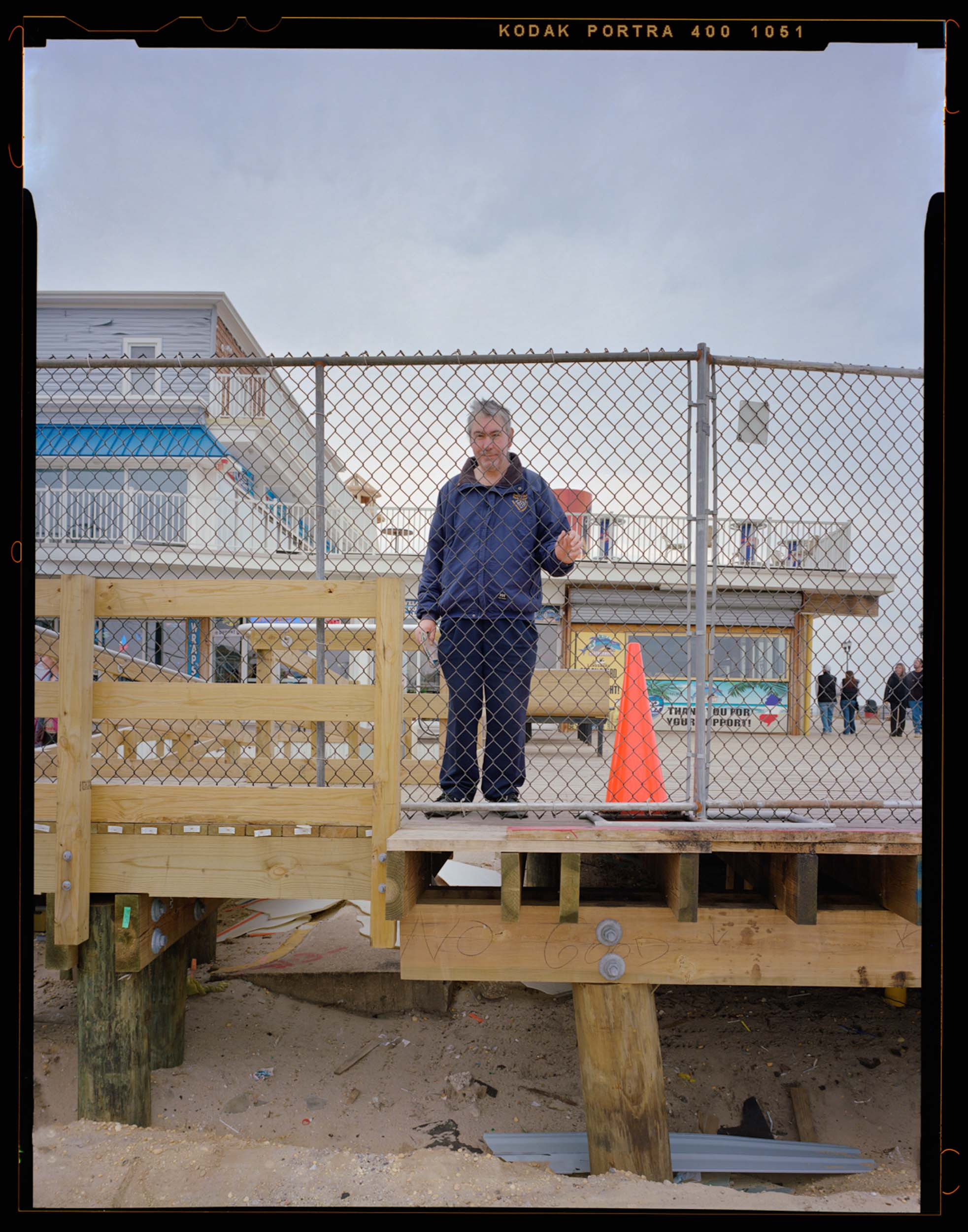 Barry, Seaside, NJ. 2014. 4x5 Shen-Hao,    A Seaside native, Barry, has been a center point in my documentation of Seaside. Barry was the guy to know in Seaside, as he knew everyone and everything about the boardwalk. As soon as I connected with Barry, people took notice and became more comfortable with my project. Being so invested in the boardwalk, Barry quickly took interested in my project and helped me as much as he could. During one of our conversations, Barry mentioned his mom always wanted a photograph of him on his second home, the boardwalk. Without hesitation, I asked if I could take his picture. Barry asked me what he should do in the photo, and I told him to just be himself. He grabbed a hold of the fence while I was framing the picture under the dark cloth and it was just perfect. When I returned the next month I printed his mother this photo.