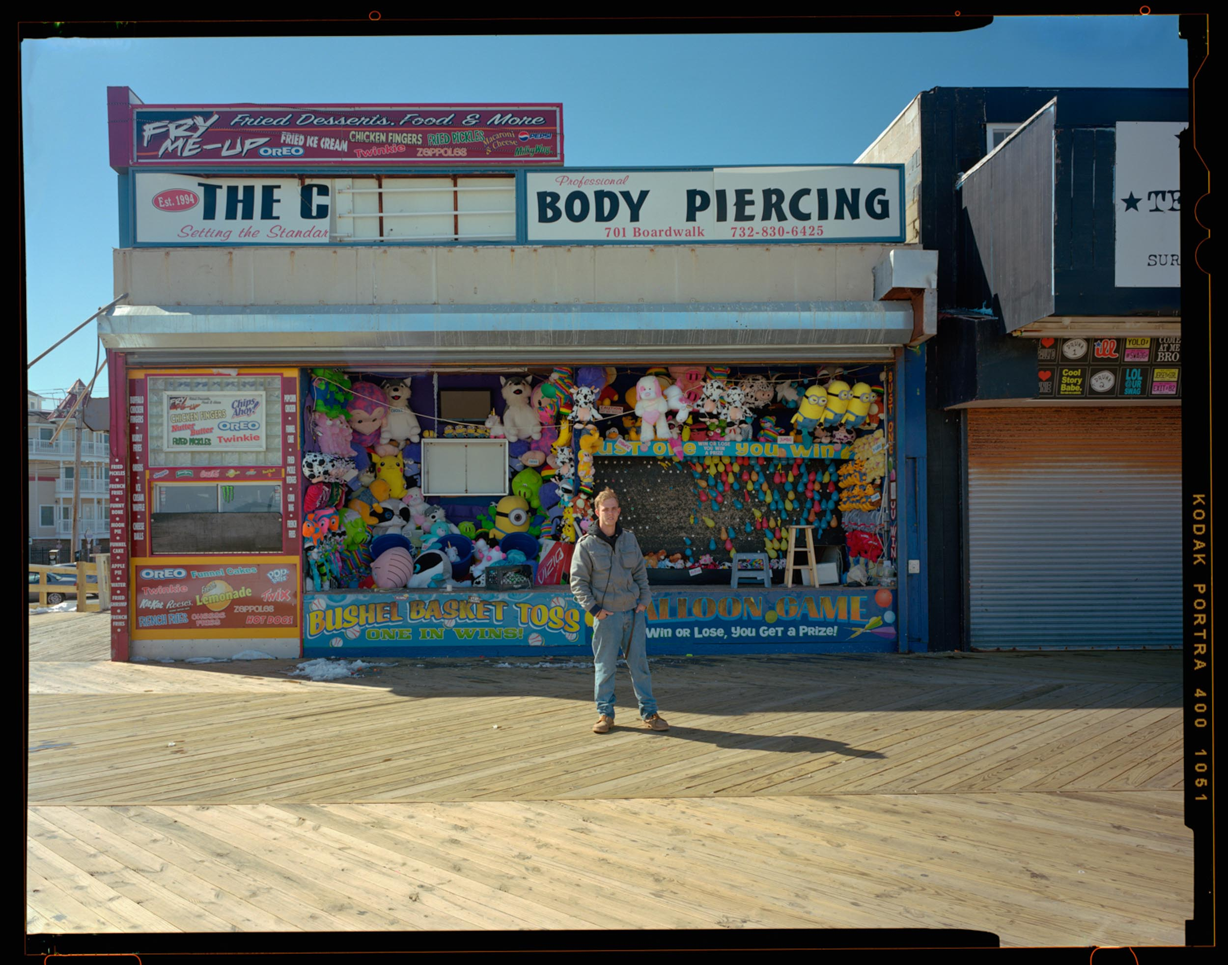 Body Piercing, Seaside, NJ. 2014. 4x5 Shen Hao    It was a bright sunny cold day as I was walking down the boardwalk with my 4x5 camera on my shoulder. I said hello and the man at the shop took interest in my camera. After talking and he told me he had interest in photography so I showed him how the camera worked. He eventually asked me what I was doing, so I explained and asked if he would mind standing for a portrait. He was hesitant at first so I pulled back and tried to capture the whole place along with him so he would feel more comfortable. I actually never caught his name. Nice Kid.