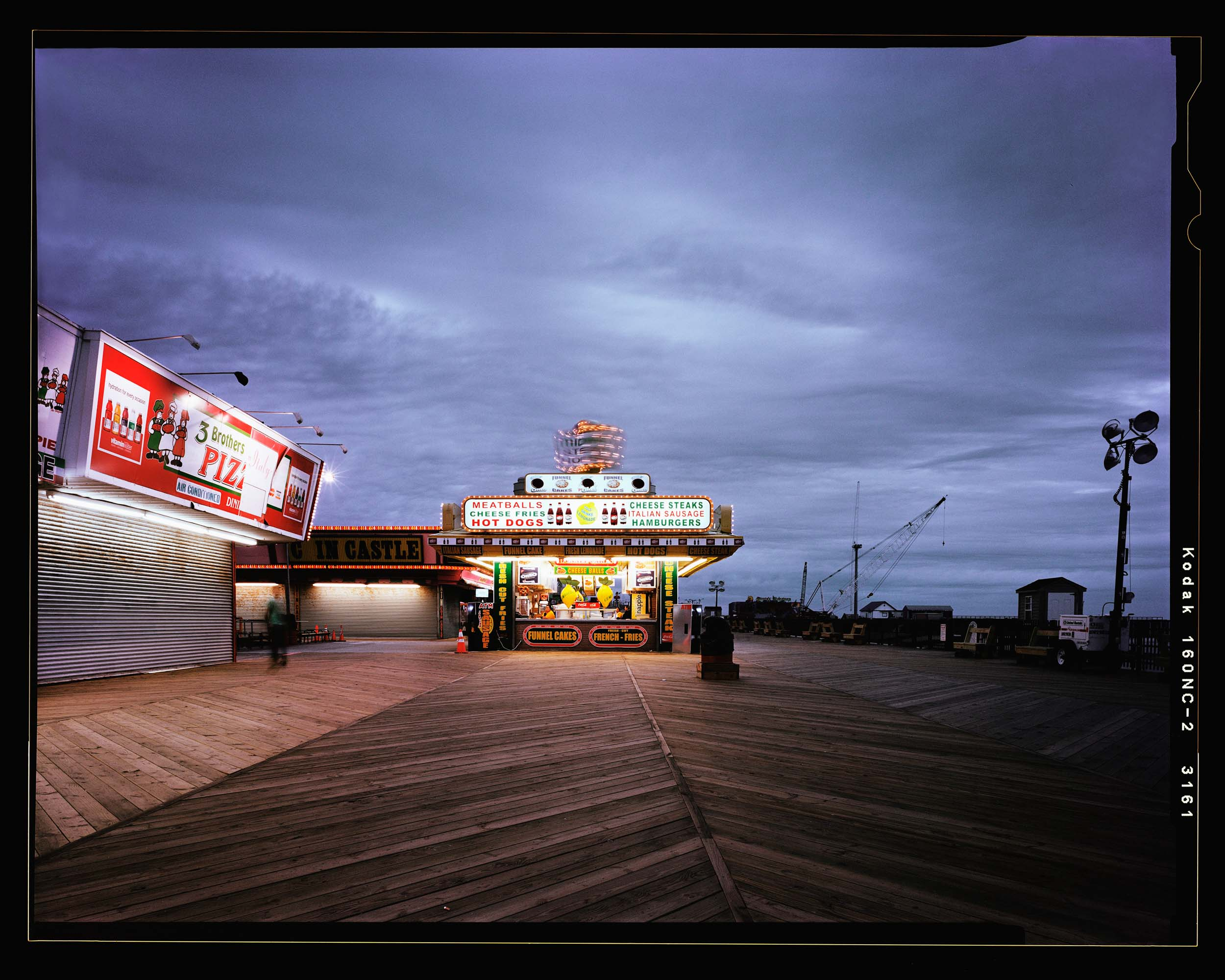 Midway, Seaside,  NJ. 2012. 4x5 Shen Hao.    This is the photograph that started the whole project. I love this photograph. The sunset light fading combined with the lights and glowing signs along with the crane showing the rebuilding in the background make this one of my favorite images. Also, the cheese steaks and sausage sandwiches are pretty fantastic.