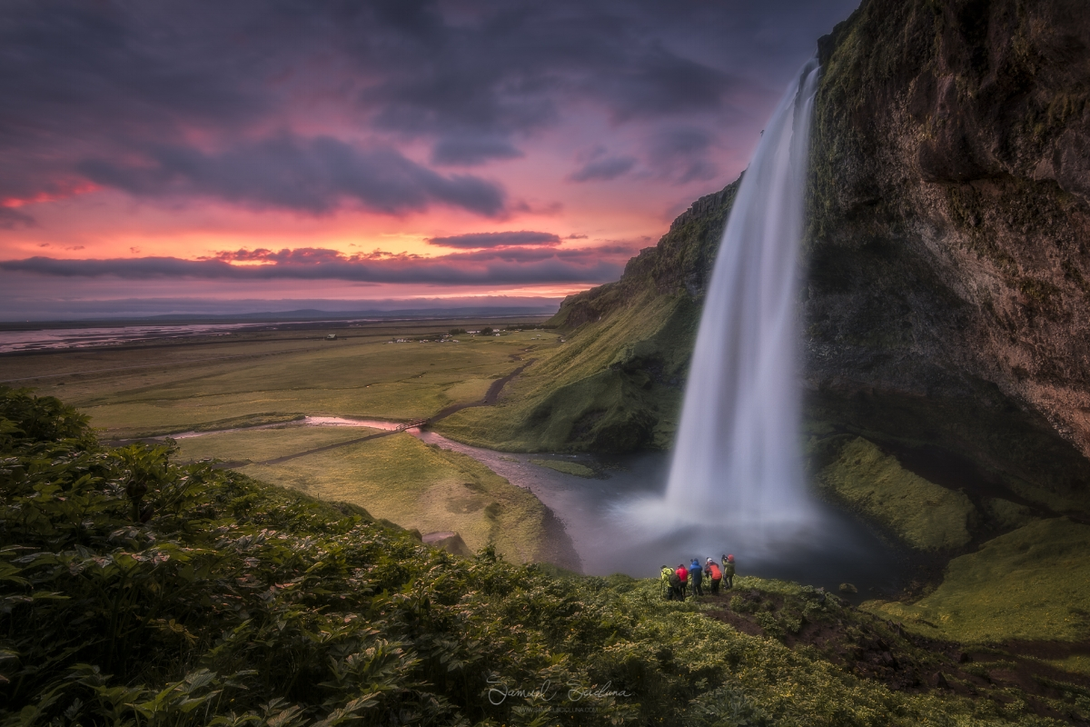 An epic fiery sky just after sunset at Seljalandsfoss waterfall in Iceland.