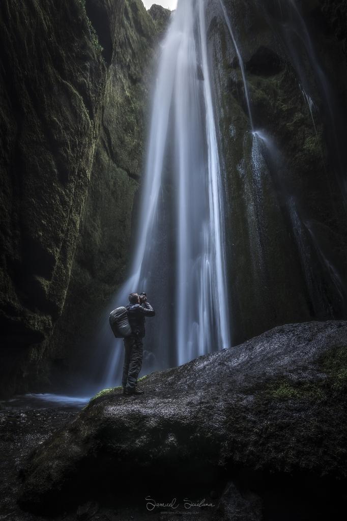 A photographer in the very wet Gljúfrabúi canyon.