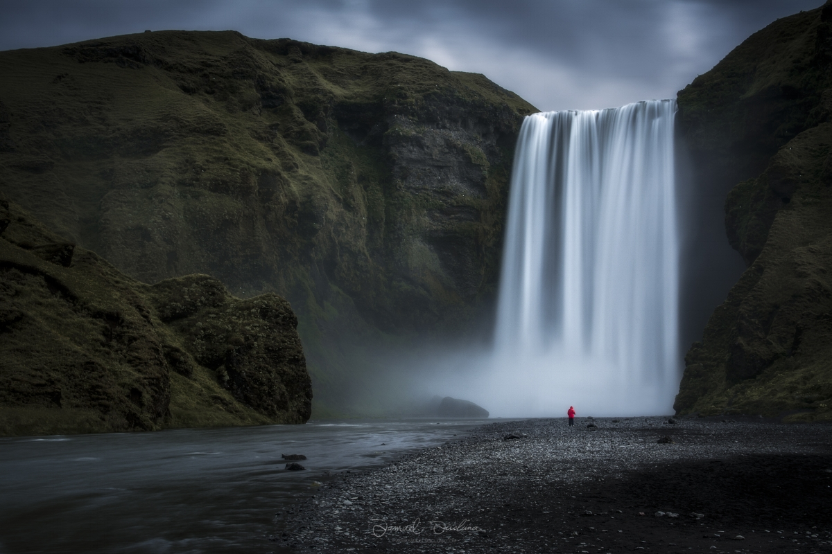 A lone tourist stands beneath the mighty Skogafoss waterfall.