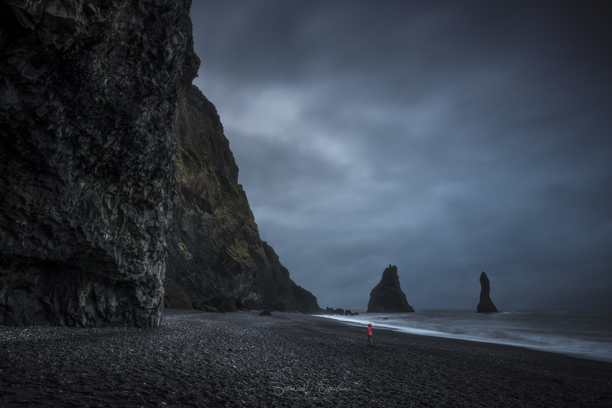 The mighty Reynisdrangar cliffs and sea stacks hang high above a tourist.