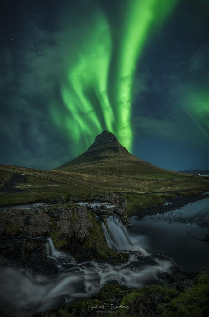 Aurora bands dance above Kirkjufell with Kirkjufellsfoss waterfall in the foreground.