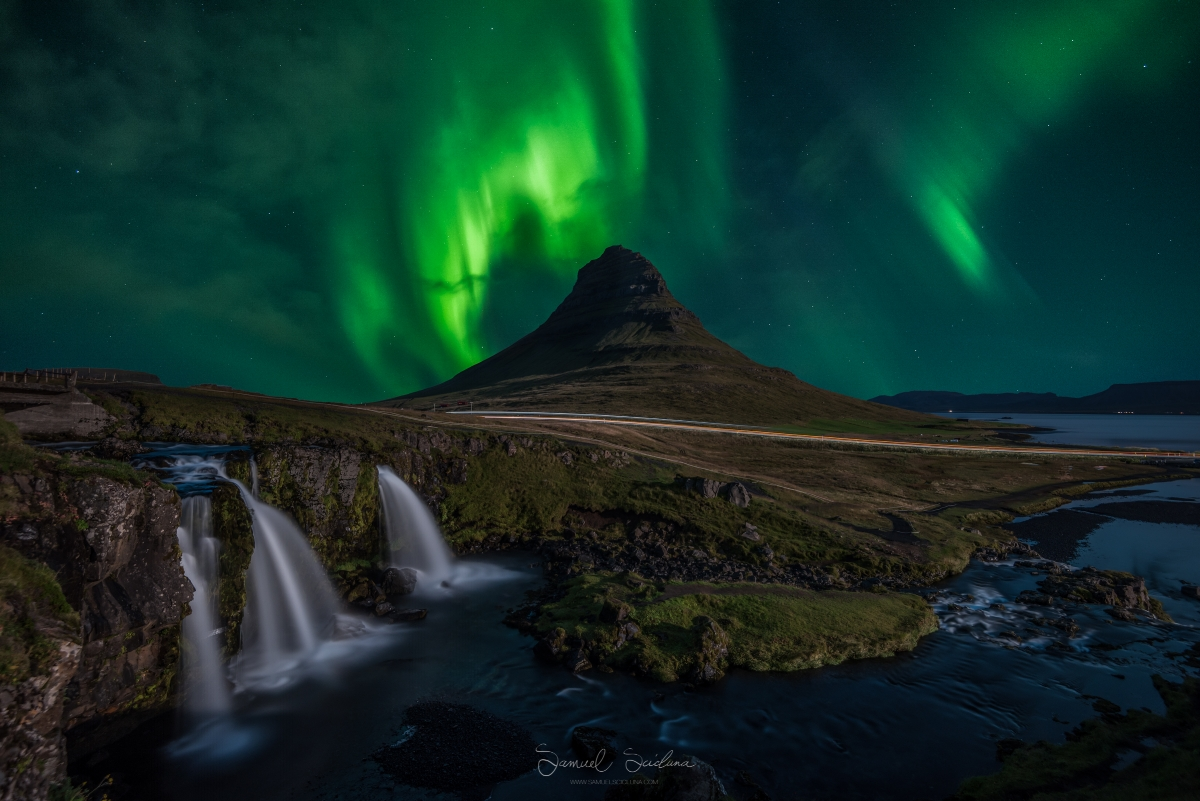 Thin clouds roll in as the Northern lights dance above Kirkjufell mountain.
