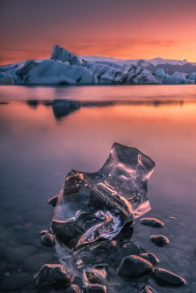 A block of crystal clear ice sits on the shore of Jökulsárlón glacier lagoon.