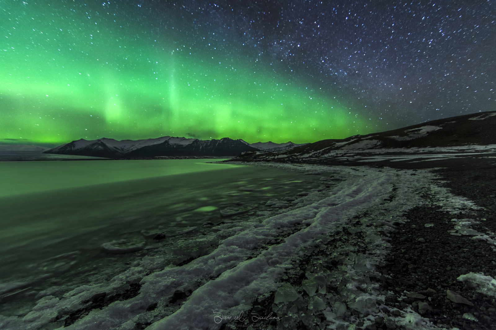 The Northern Lights mirror the shape of the banks of Jökulsárlón glacier lagoon.