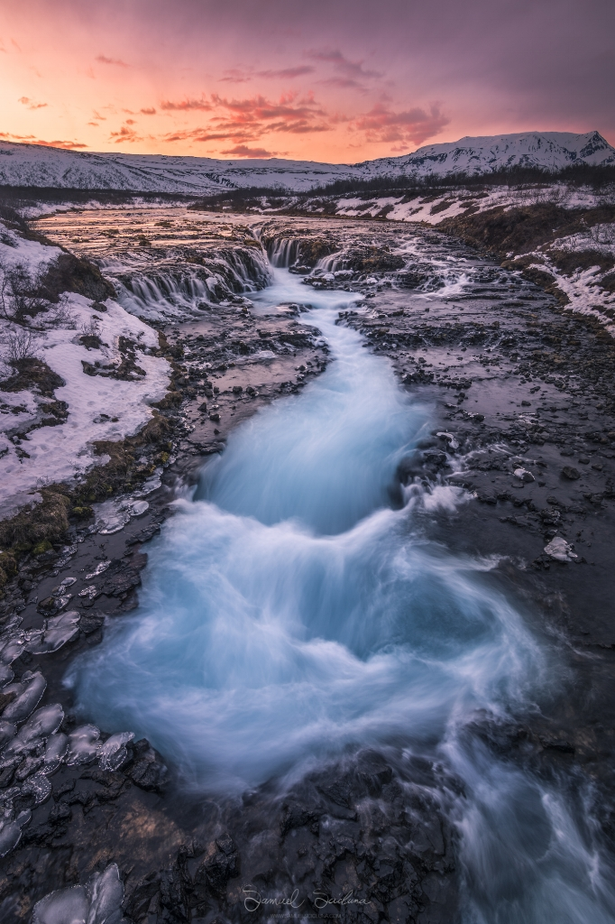 The warm colors of sunset reflect off the snow along the banks of Bruarfoss, the famous blue waterfall!