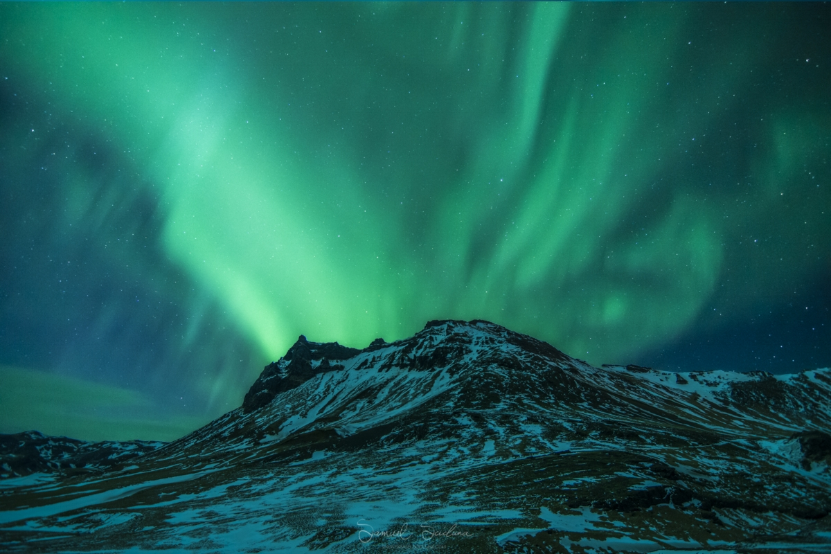 An explosion of Auroral activity behind a random mountain in Iceland.