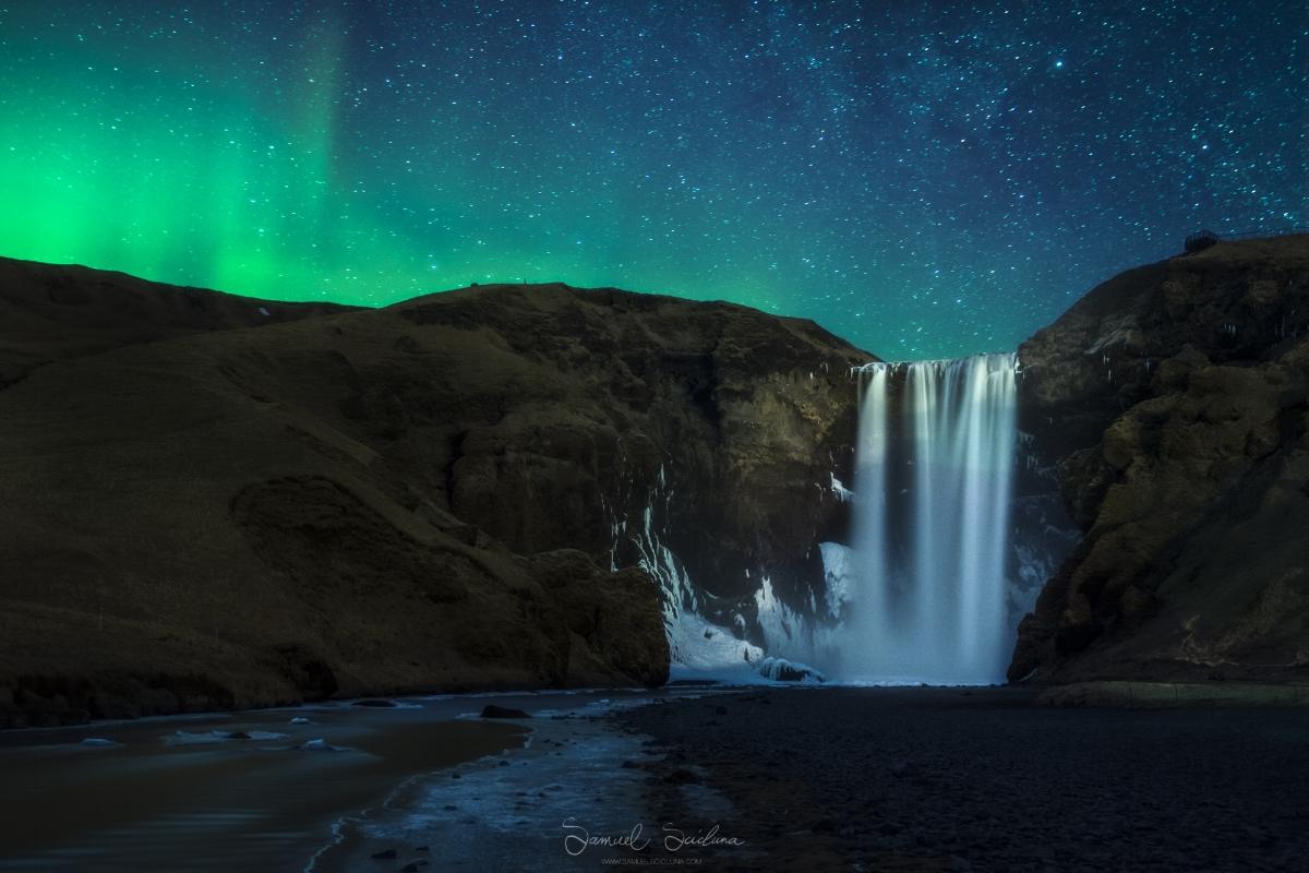 Very faint KP1 - KP2 Auroras glow in the night sky behind Skogafoss waterfall in Iceland.