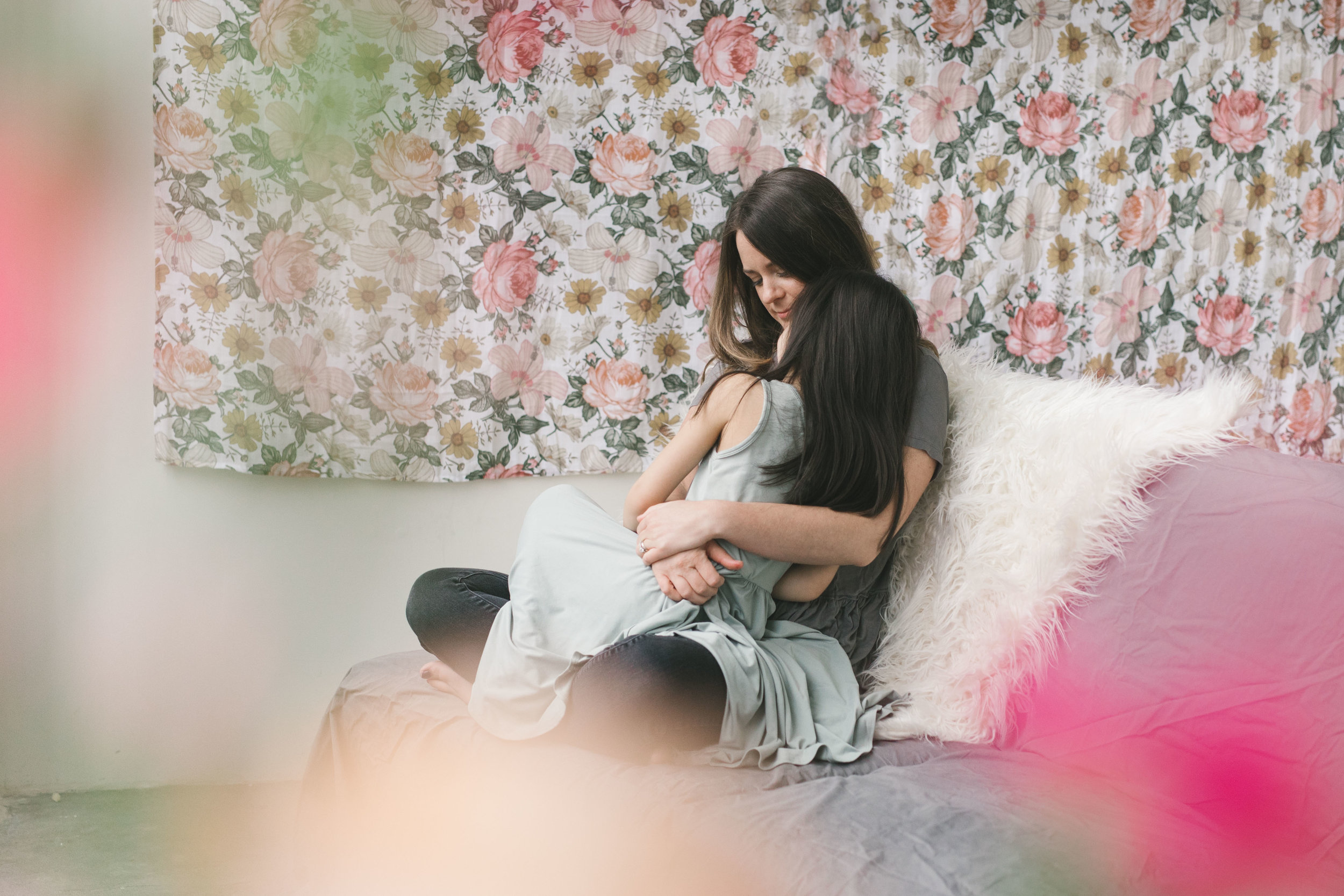 A cuddly and feminine mother daughter session in a Seattle studio with flowers by Chelsea Macor Photography