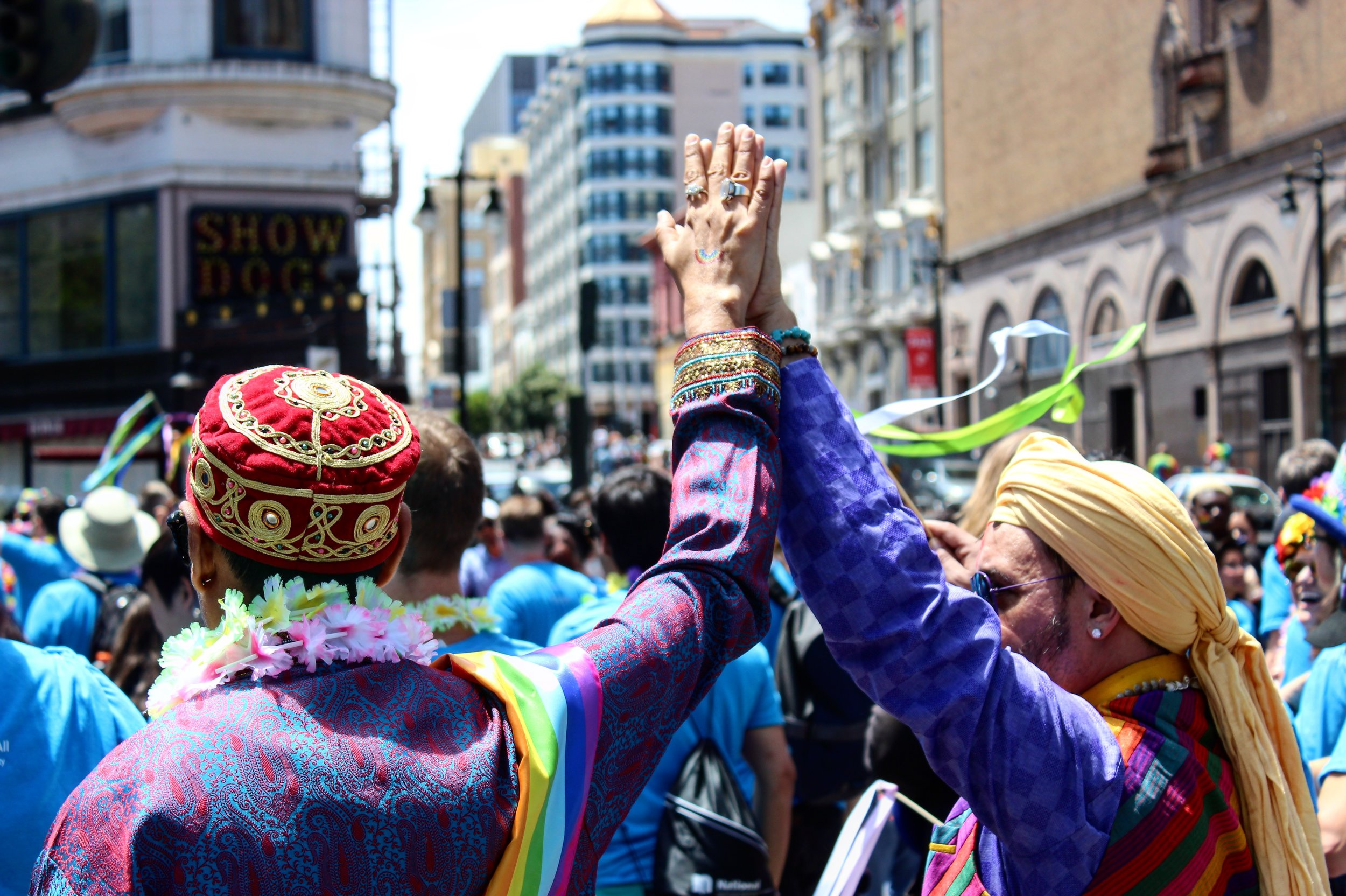 Two men raise their hands together in unity during the 2017 San Francisco Pride Parade.