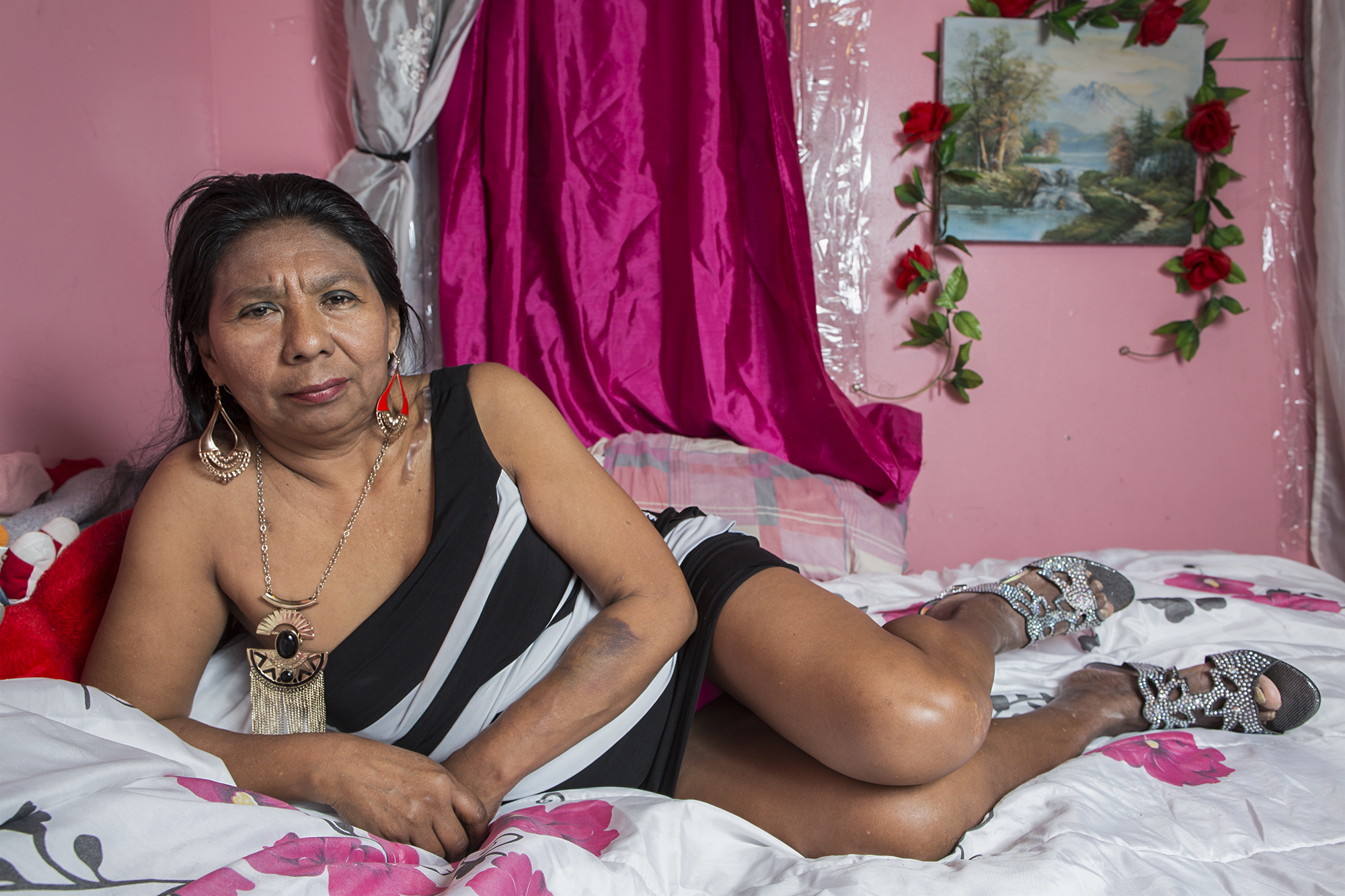 """Dionisia Martínez, in her bedroom on 45th Street in Sunset Park, Brooklyn. She is a singer and dancer of Mexican folklore. Born in Atencingo, Puebla, she has been based in New York since 2002. Since then she has worked washing dishes in restaurants, selling balloons, and cleaning, but her passion is singing. She is better known as """"Lupe Cantarrecio"""" (Lupe """"who sings out loud""""). She has a role in the documentary """"Me Voy"""" (I go) directed by the film-making collective Mu Media."""