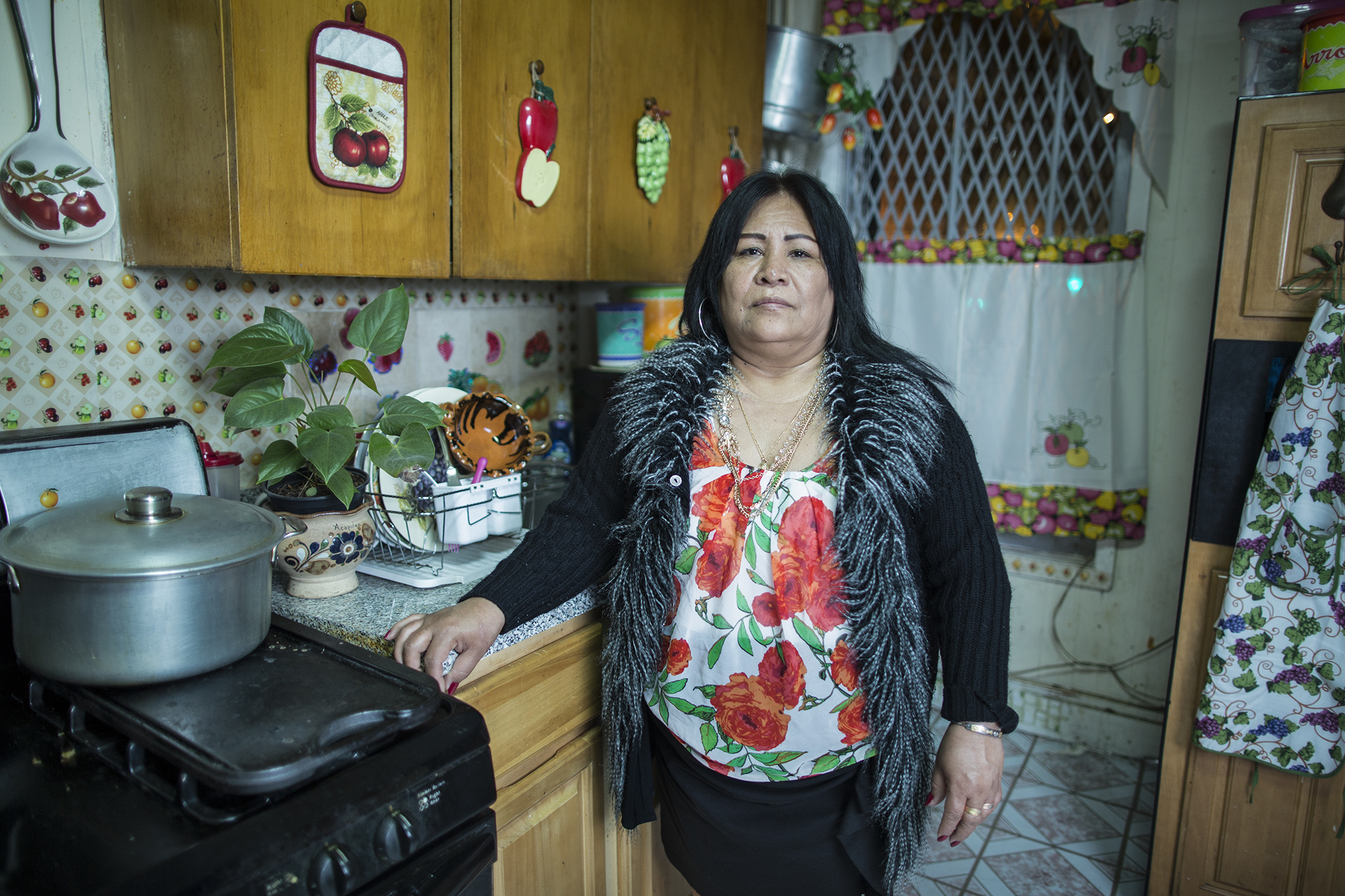 """Juanita Torres de León in the kitchen at her home on 59th Street, Sunset Park, Brooklyn. She was born in Atencingo, Puebla, but for 27 years she has lived with her whole nuclear family in Sunset Park. Juanita is a member of Saint Jacobi's Church and coordinator of the community kitchen. Juanita was part of the team that eventually came to be known as """"Occupy Sandy"""" in 2012, feeding the volunteers who were helping hurricane victims."""