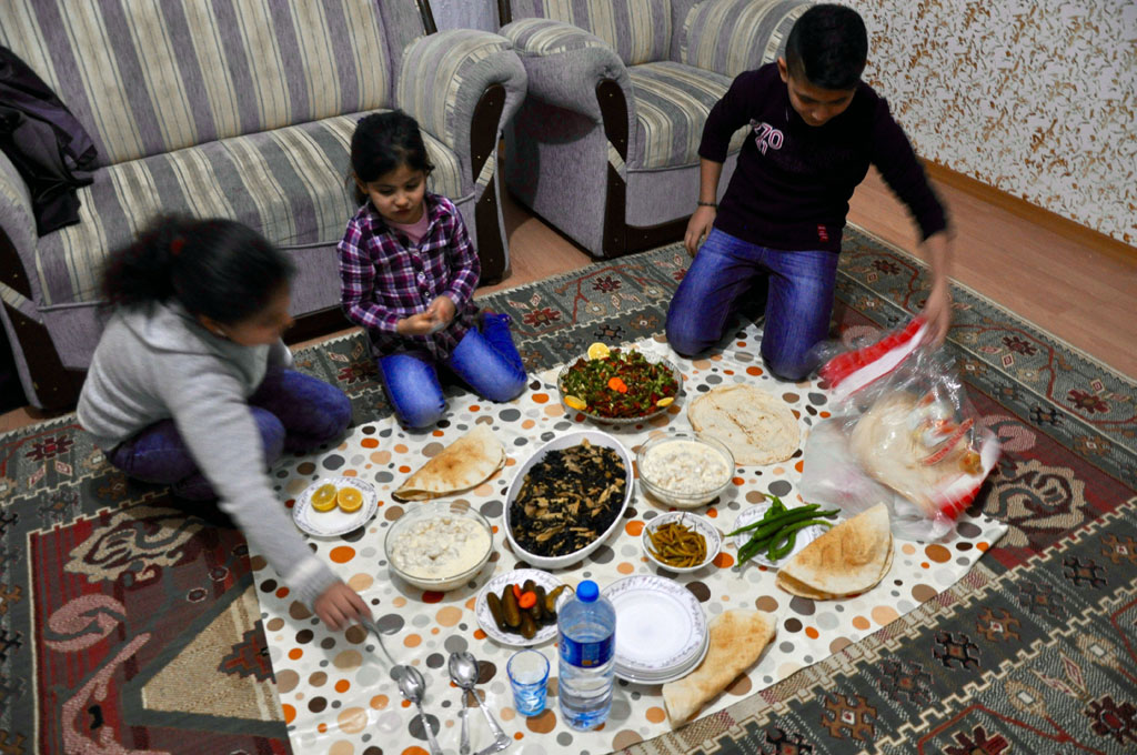 The Sheikho children Ruseel, Rivana and Rubi gather for dinner before they take the boat journey to Greece.   (Photo by Lauren Bohn/GroundTruth)